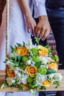 Букет невесты из бело-зеленых и оранжевых цветов на фоне жениха и невесты, держась за руки