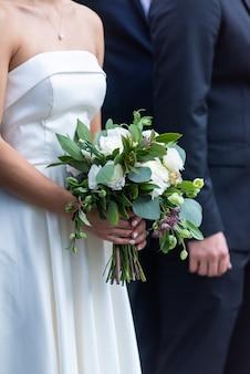 Невеста в красивом белом свадебном платье с букетом невесты стоит рядом с женихом