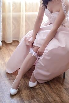 베이지 색 드레스를 입은 신부는 아침에 방에서 다리에 흰색 레이스 웨딩 가터를 착용합니다.