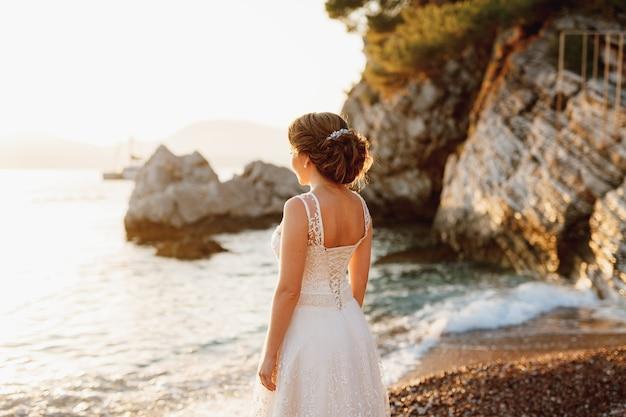 섬세한 드레스를 입은 신부가 절벽 근처의 자갈 해변에 서서 먼 곳을 바라본다.