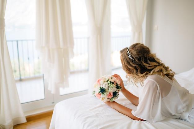 Невеста в нежном пеньюаре с букетом в руках лежит на кровати у окна с белыми занавесками. фото высокого качества