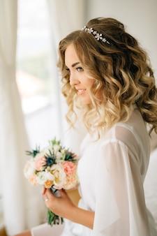흰색 커튼으로 창가에 앉아 웃고, 근접 촬영 그녀의 손에 꽃다발과 함께 부드러운 실내의 신부