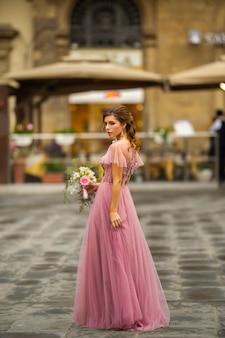 Невеста в розовом платье с букетом стоит в центре старого города флоренции в италии.