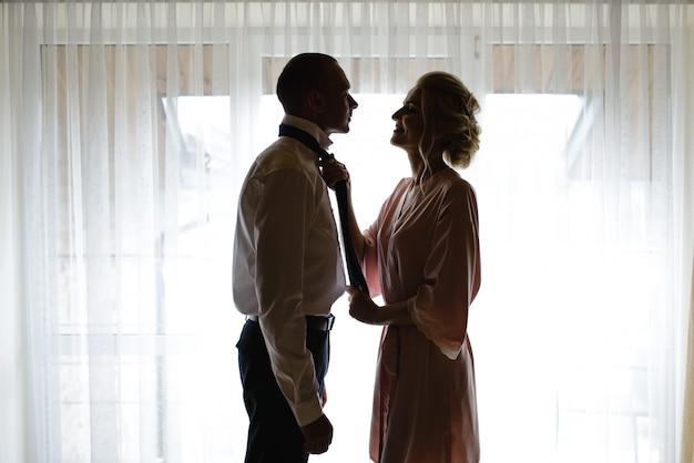 실크 가운을 입은 신부는 신랑에게 넥타이를 꽂는 데 도움이됩니다. 신부와 신랑이 함께 결혼식을 준비하고 있습니다