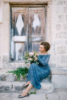 그녀의 손에 꽃다발과 함께 세련된 파란색 드레스를 입은 신부가 오래된 나무 문 근처 계단에 앉습니다. 고품질 사진
