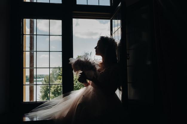 ウェディングドレスと花束を着た花嫁が開いた古い窓に座って見える