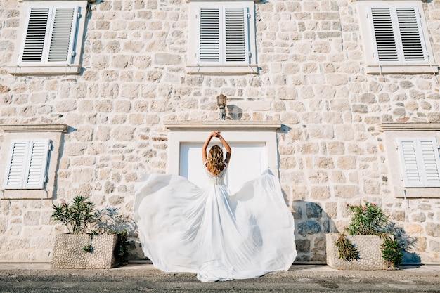웨딩 드레스를 입은 신부가 perast의 옛 거리에서 빙빙 돌고 있고 그녀의 치마는 바람에 펄럭입니다