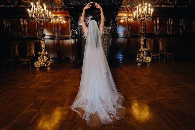 ウェディングドレスを着た花嫁が、城の古代の内部に背を向けて立っています。