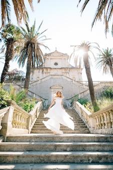 웨딩 드레스를 입은 신부가 prcanj에있는 사원의 고대 계단에서 소용돌이 치고, 그녀의 치마는 바람에 펄럭입니다.