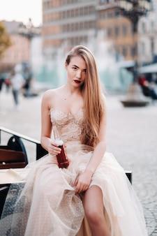 ヴロツワフの旧市街にある長い髪と飲み物のボトルのウェディングドレスを着た花嫁。ポーランドの旧市街の中心部での結婚式の写真撮影。ポーランド、ヴロツワフ。
