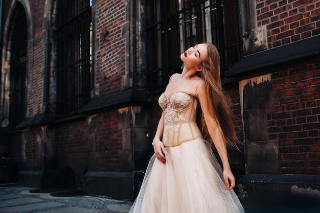Невеста в свадебном платье с длинными волосами в старом городе вроцлав. свадебная фотосессия в центре древнего города в польше. вроцлав, польша.