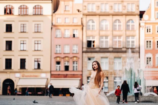 ヴロツワフの旧市街で長い髪のウェディングドレスを着た花嫁。ポーランドの古代都市の中心部での結婚式の写真撮影。ポーランド、ヴロツワフ。