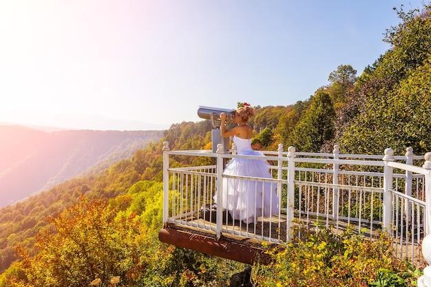 Невеста в белом платье на смотровой площадке смотрит в бинокль стационарного бинокля.