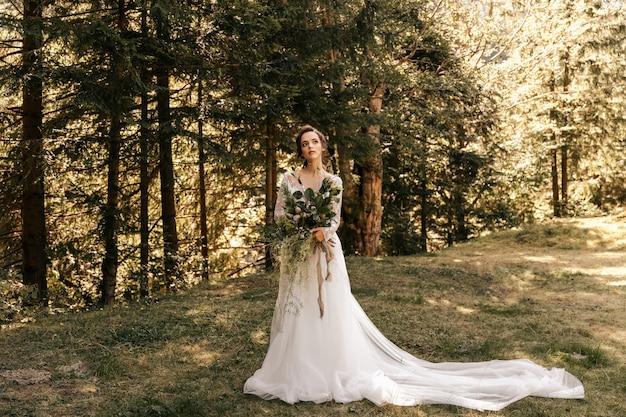 白いドレスを着た花嫁が美しいウェディングブーケを持って森の中に立っています