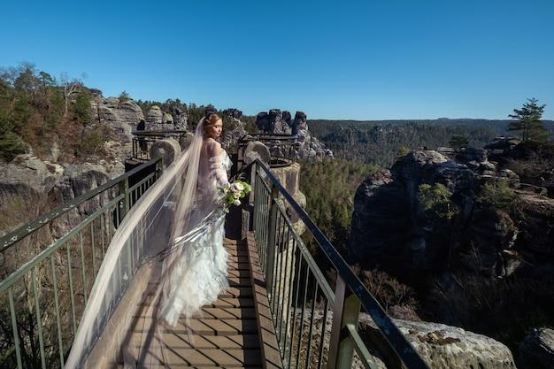 스위스 작센, 독일, 바스테이의 산과 협곡 배경에 꽃다발을 얹은 하얀 드레스를 입은 신부.