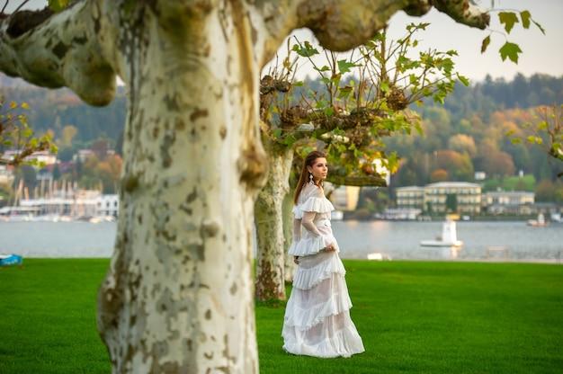 해질녘 큰 나무가 있는 오스트리아 마을의 공원에서 하얀 웨딩드레스를 입은 신부.