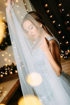 Невеста в вечернем синем платье стоит с закрытыми глазами и мечтает