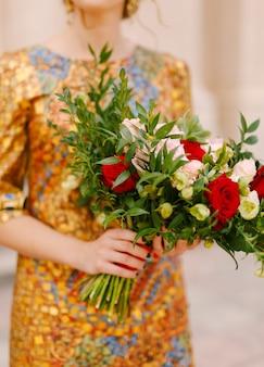 Невеста в необычном золотом платье держит в руках букет невесты из белых и красных роз.