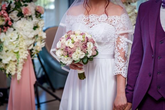 花嫁は手にバラとウェディングブーケを持っています。