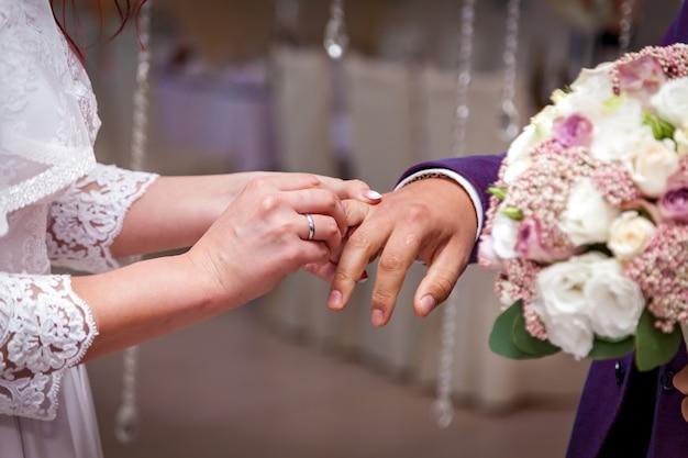 결혼식 중 신랑의 손가락에 반지를 끼고 있는 신부.