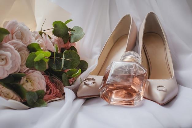 Туфли невесты со свадебным букетом и духами на фате. свадебная концепция