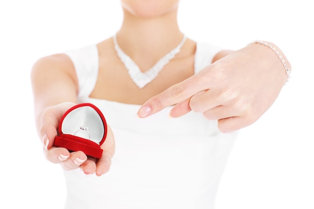 Невеста показывает обручальное кольцо в красной коробке
