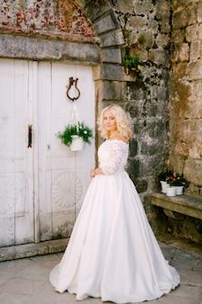 Невеста стоит перед старым кирпичным зданием возле белой деревянной двери с цветочными горшками в перасте.
