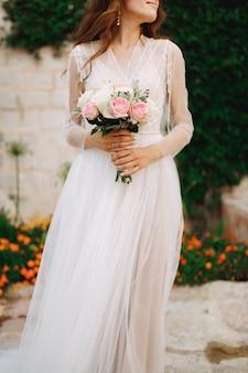 Невеста с букетом в руках стоит у стены дома с зеленой лианой и апельсином