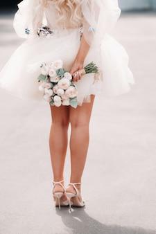 짧은 웨딩 드레스를 입은 신부가 등 뒤에 꽃다발을 들고 있습니다.