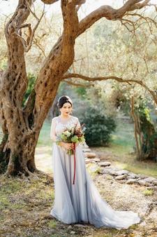 オリーブの木立の美しいオリーブの木の下に、ウェディングブーケを持った花嫁が立っています。