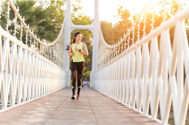 木製の橋の上を走っている明るい美しい女性