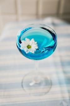 Ярко-синий коктейль в бокале nick and nora, украшенный цветком ромашки