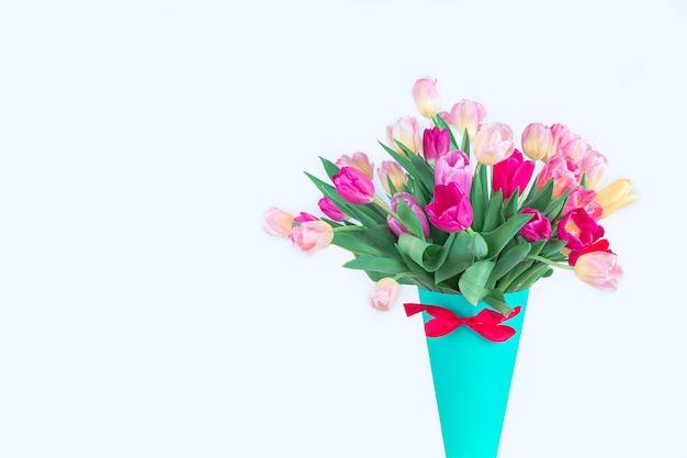 青い紙の花瓶にチューリップの明るい花束