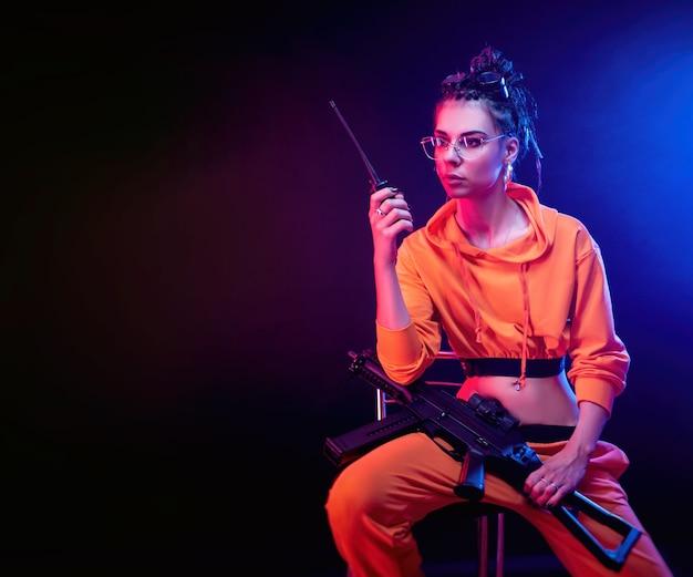 네온 불빛의 어두운 배경에 기관총이 달린 주황색 점프수트를 입은 밝은 갈색 머리. 라디오에서 말하는