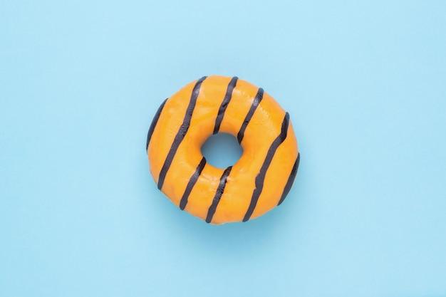 青い背景に明るい炭酸オレンジドーナツ。おいしい人気のペストリー。