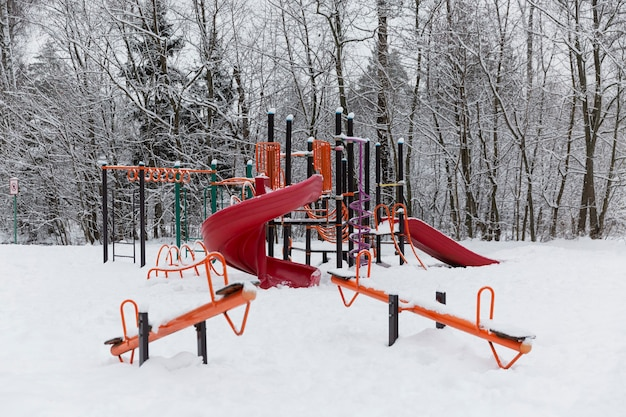 Яркая детская площадка в снегу на фоне леса.