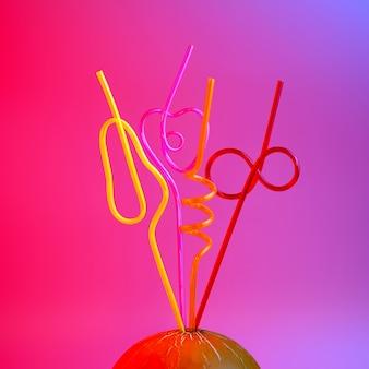Яркие цветные коктейльные трубочки застряли в дыне на розовом
