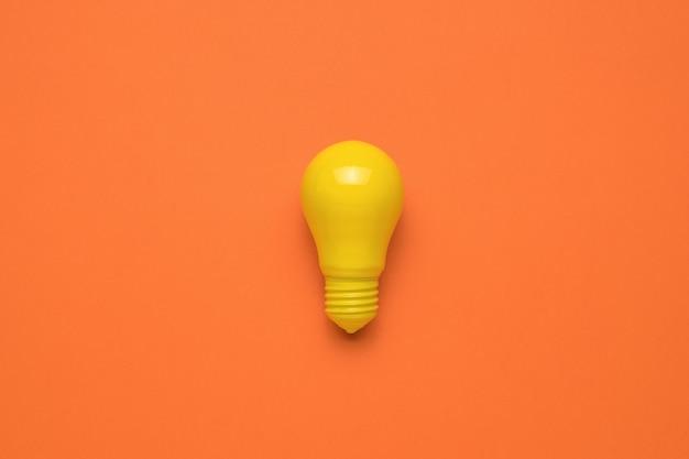 オレンジ色の背景に明るい創造的な黄色の電球。ミニマリズム。エネルギーとビジネスの概念。フラットレイ。