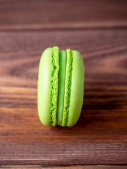 Яркое вкусное сладкое миндальное печенье зеленого цвета лежит на коричневом деревянном фоне. вертикальное фото