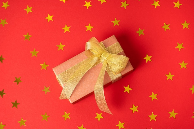 Яркий подарок в золотой упаковке с золотым бантом на цветном фоне со сверкающими звездами
