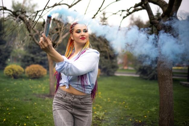 푸른색 셔츠에 반짝이 화장과 아프리카 머리띠를 한 밝은 소녀가 푸른 나무로 가득한 공원에서 인공 연기로 피난처를 얻습니다