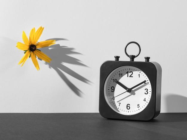 明るいオレンジ色の花と時計の白黒画像。