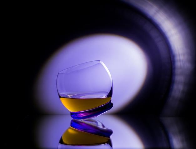 Яркий круглый бокал шлепанца с виски на черной зеркальной поверхности с отражением в луче пурпурного клубного света Premium Фотографии