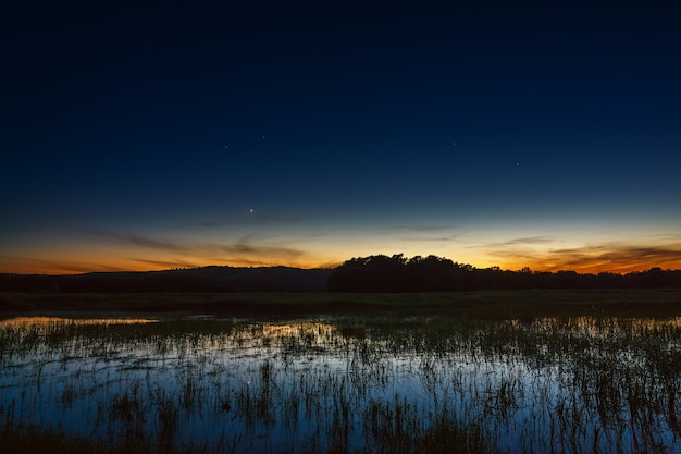 Яркий закат в ночном небе. на длинной выдержке запечатлен пейзаж с рекой и деревьями.