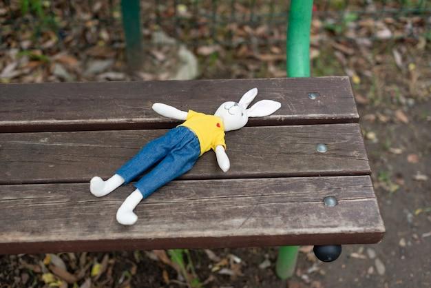 밝은 장난감 토끼는 아이가 남긴 놀이터의 나무 벤치에 누워 있다