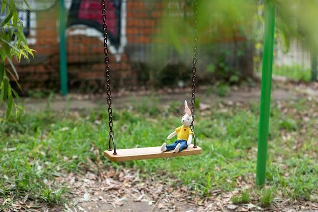 밝은 장난감 토끼는 아이가 남긴 놀이터의 나무 그네에 누워 있다