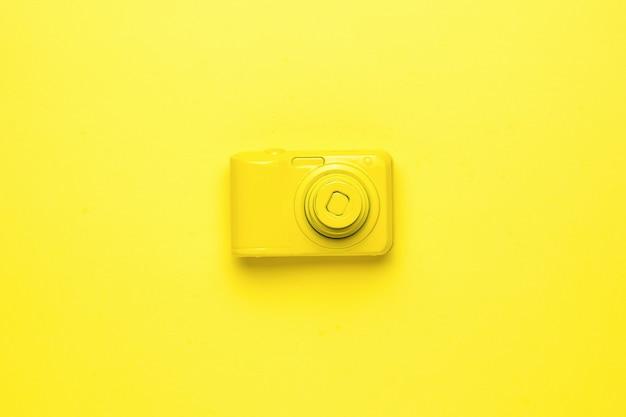 明るい黄色の背景に明るい黄色のカメラ。写真機材のモノクロ画像。フラットレイ。