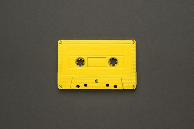 회색 배경에 자기 테이프가 있는 밝은 노란색 카세트. 음악을 듣기 위한 세련된 복고풍 장비. 플랫 레이.