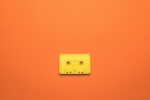 주황색 배경에 자기 테이프가 있는 밝은 노란색 카세트. 음악을 듣기 위한 세련된 복고풍 장비. 플랫 레이.