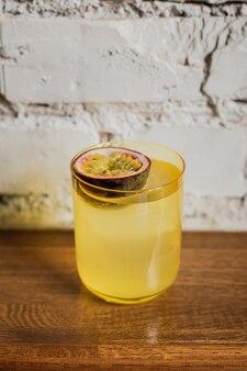 Ярко-желтый коктейль со льдом в низком бокале со льдом, украшенный маракуйей.
